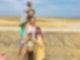 Ein Mann und eine Frau stehen an einem Strand. Auf den Schultern des Mannes sitzt ein kleines Kind. vor der Frau stehen zwei kleine Mädchen.