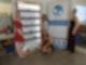 Drei Frauen stehen um ein Regal und ein Plakat, auf dem Veggie Ponics steht. Eine vierte Dame kniet davor. Alle lächeln in die Kamera.