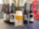 In der Mitte des Bildes steht ein mit Bier gefülltes Glas. Links von dem Glas sind drei dunkelbraune Bierflaschen, rechts von dem Glas befinden sich zwei Bierflaschen. Jede Flasche hat ein anderes Label.