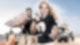Eine Frau mit Flensburger Flasche und ein Mann mit Harke stehen am Strand im Vordergrund. Im Hintergrund sind noch mehr Menschen sowie Trecker und Mülltüten zu sehen.