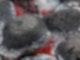 Im Bild sind runde, heiße Kohlen zu sehen, außen schwarz, innen weiß und glühend.
