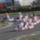 Auf einer breiten, asphaltierten Straße fahren sechs Karts ein Rennen. Die Fahrer tragen Helme und Rennanzüge.
