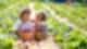 Auf einem Feld sitzen zwei Kinder nebeneinander in der Sonne. Auf ihrem Schoß haben sie geflochtene Körbe, in denen Erdbeeren liegen.