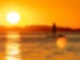 Die Sonne scheint golden auf Wasser, auf dem sich ein Stand-Up-Paddler fortbewegt.