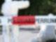 Menschen in weißen Schutzanzügen stehen und knien hinter einem rot-weißen Absperrband mit der Aufschrift Polizeiabsperrung.
