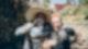 Zwei Menschen stehen Arm in Arm, mit Wassergläsern in der Hand.