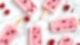 Auf weißem Grund liegen sechs rosafarbene Eis am Stiel und einige Himbeeren verstreut.