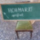"""Auf einem braunen Holzstuhl mit grünem Samtpolster steht eine grüne Tafel. Darauf steht mit weißer Kreide """"Flohmarkt geöffnet"""" geschrieben."""