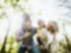 Eine Familie bestehend aus zwei Kindern und zwei Erwachsenen steht in einem Wald und lacht sich an.