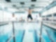 Der Bildausschnitt zeigt ein Sprungbrett in einem Hallenbad, von dem ein Junge mit Badekappe springt.