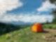 An einem Berghang steht ein orangenes Zelt. Dahinter sieht man ein Bergpanorama.
