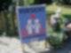 """Ein Plakat mit der Aufschrift """"Vorsicht Schulkinder"""" steht auf Schotter vor einem Garten."""