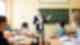 Eine Lehrerin steht vor einer beschrifteten Tafel und schaut die vier Schüler an, die an ihren Tischen sitzen. Alle tragen Atem-Masken.