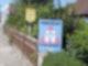 """Ein Plakat mit der Aufschrift """"Vorsicht Schulkinder"""" steht auf einem Gartenzaun an einer Straße."""