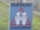 """Ein Plakat mit der Aufschrift """"Vorsicht Schulkinder"""" lehnt an einem Briefkasten."""
