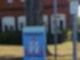 """Ein Plakat mit der Aufschrift """"Vorsicht Schulkinder"""" hängt an einem Zaun unter einem Straßenschild mit der Aufschrift """"Schulstraße""""."""