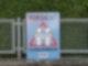 """Ein Plakat mit der Aufschrift """"Vorsicht Schulkinder"""" lehnt einem Zaun vor einer Hecke."""