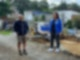 Vor einer Baugrube stehen ein Mann in Jacke und Shorts und eine Frau in R.SH Jacke.