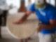 EIn Mann mit Atemschutzmaske steht mit Schleifpapier an einem Surfboard aus Holz und schleift es ab.