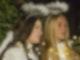 Zwei als Engel verkleidete junge Frauen stehen draußen und blicken in die Ferne.