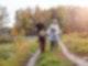 Zwei Erwachsene und zwei Kinder laufen einen Feldweg entlang. Die Bäume und Sträucher im Hintergrund sind herbstlich bunt gefärbt.
