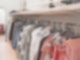 Auf einer langen Kleiderstange hängen an Bügeln viele verschiedene Klamotten.