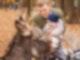Ein Vater hält sein kleines Kind im Arm, während die beiden einen Esel streicheln.