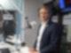 Ein Mann in mittlerem Alter, ist mit Anzug und Hemd bekleidet. Er sitzt in einem Studio vor einem Mikrofon und schaut in die Kamera.