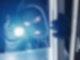 Ein Mann mit einer schwarzen Maske und eine Taschenlampe leutet durch ein Fenster.