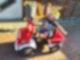 Ein kleiner Junge mit Feuerwehr-Helm sitzt auf einem kleinen Spielzeug-Feuerwehrauto und reckt eine Hand freudig in die Luft.