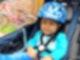 Ein kleiner Junge mit Helm sitzt angeschnallt in einem Fahrradanhänger.