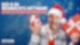Ein Mann mit Weihnachtsmannmütze hält zwei rot eingepackte Geschenke in den Händen und strahlt in die Kamera.
