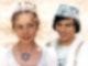 Eine Prinzessin und ein Prinz, beide edel in weiß gekleidet, stehen vor hell glitzerndem Hintergrund.