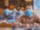 Mehrere Schülerinnen und Schüler sitzen an Tischen mit Masken und schauen in Richtung ihrer Lehrer.