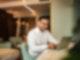 Ein dunkelhaariger Mann sitzt lachend vor einem Laptop. Im Hintergrund ist ein Hotelzimmer zu sehen.