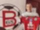 Ein junger Mann schaut in die Kamera und hält dabei ein rotes Fußball-Trikot hoch.