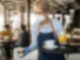 Eine blonde Frau mit FFP2-Maske und Schürze hat ein Tablett in der einen und einen Nachtisch in einem Glas in der anderen Hand.