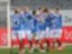 Eine Spielertraube in blauen Trikots steht beieinander und klatscht sich ab.