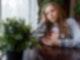 Junges Mädchen sitzt mit Handy in der Hand am Fenster