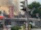 Zwei Feuerwehrmänner stehen vor einem ausgebrannten und qualmenden Supermarkt.