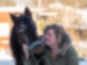 Eine Frau in Winterjacke schaut auf ein braunes Pony und hält es am Halfter