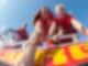 Menschen mit Schwimmwesten auf einem Boot ziehen eine Person aus dem Wasser.