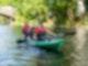 Zwei Menschen in einem grünen Kajak fahren über einen Fluss.