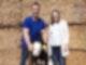 Ein Mann und eine Frau stehen mit einem Kalb vor einer Wand aus Heu.
