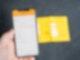 Ein gelber Impfausweis liegt auf dem Tisch, im Vordergrund ist ein Smartphone mit dem digitalen Impfpass zu sehen