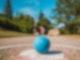 Ein blauer Golfball liegt auf einem Platz. Im Hintergrund spielen Menschen Minigolf.
