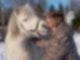 Ein Mann in brauner Winterjacke kuschelt mit einem weißen Pony.
