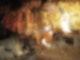 Vor einer Kulisse ist ein brennender Ölturm mit Häusern und verkleideten Menschen zu sehen.