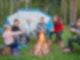 Kinder sitzen vor einem Zelt im Halbkreis um ein Lagerfeuer und grillen Marshmallows am Stock.