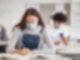 Ein Mädchen sitzt mit Maske an einen Tisch über ein Buch gebeugt und schreibt in ein Heft. Im Hintergrund ist ein Klassenraum zu sehen.
